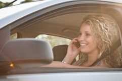 Portrait of young smiling woman driving car Stock Photos