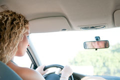 Portrait of young smiling woman driving car Royalty Free Stock Images