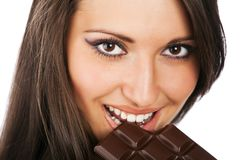 Portrait of young smiling woman eating chocolate Royalty Free Stock Photos