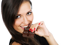 Portrait of young smiling woman eating chocolate Stock Images