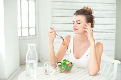 Portrait of a young smiling woman eating a fresh salad in white room. Stock Images