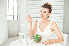 Portrait of a young smiling woman eating a fresh salad in white room. Stock Photo
