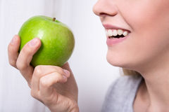 Portrait of young smiling woman eating green apple Royalty Free Stock Images