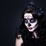 Portrait of young smiling woman with Halloween skull make up ove Stock Images