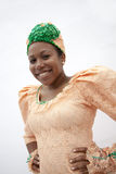 Portrait of young smiling  woman with hands on hips in traditional clothing from the Caribbean, studio shot Stock Photo