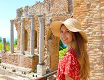 Portrait of young smiling woman with hat in famous Taormina Greek Theatre, Sicily, Italy royalty free stock photo