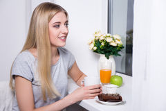 Portrait of young smiling woman having breakfast in kitchen Royalty Free Stock Photography