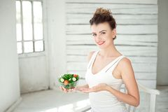 Portrait of a young woman holding a fresh salad bowl in white room. Royalty Free Stock Photos