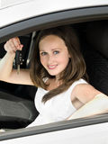 Portrait of young smiling woman holding key in his own car Stock Photo
