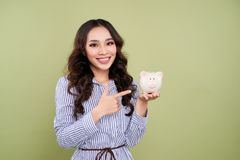 Portrait of young smiling woman holding piggy bank against green. Background Royalty Free Stock Image