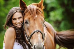 Portrait of young smiling woman with horse Royalty Free Stock Images