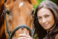 Portrait of young smiling woman with horse Royalty Free Stock Photo