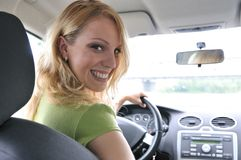 Portrait of young smiling woman inside a car. Portrait of young smiling woman siting behind steering wheel inside car Stock Images