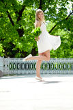Portrait of young smiling woman in jump, outdoors Stock Photography