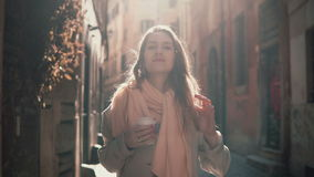 Portrait of young smiling woman looking at camera. Happy attractive girl standing in morning street, doing up hair. Portrait of young smiling woman looking at stock video