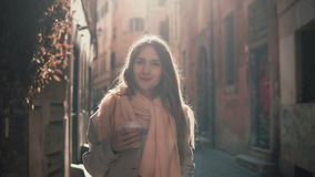 Portrait of young smiling woman looking at camera. Happy attractive girl standing in morning street, doing up hair. Royalty Free Stock Image
