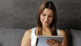 Portrait of young smiling woman looking at digital tablet. Woman with tablet pc sitting on sofa. Woman using tablet stock footage