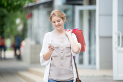 Portrait of young smiling woman looking at phone while going for Stock Photos