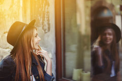 Portrait of young smiling woman looking at the shop window. Model wearing stylish wide-brimmed black hat. City lifestyle Royalty Free Stock Photo