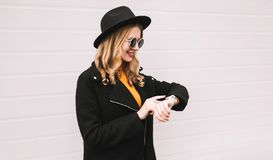 Portrait young smiling woman looking at smart watch using voice assistant or takes calling. On city street, gray wall background royalty free stock image