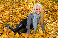 Portrait of young smiling woman on maple leaves Stock Photos