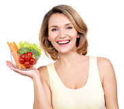 Portrait of a young smiling woman with a plate of vegetables. royalty free stock photo