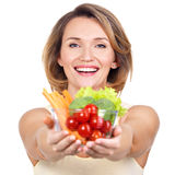 Portrait of a young smiling woman with a plate of vegetables. Stock Photo
