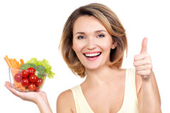 Portrait of a young smiling woman with a plate of vegetables. Stock Images