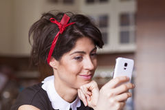 Portrait of young smiling woman receiving funny message Stock Image