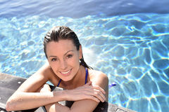 Portrait of young smiling woman relaxing in pool Royalty Free Stock Image