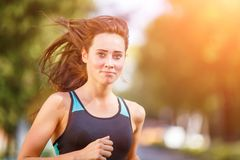 Portrait of young smiling woman running in morning Stock Image