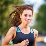 Portrait of young smiling woman running in morning Royalty Free Stock Photography