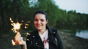 Portrait of young smiling woman with sparkler celebrating at beach party stock images
