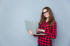 Portrait of young smiling woman standing and holding laptop Royalty Free Stock Photography