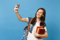 Portrait of young smiling woman student with backpack holding school books, doing taking selfie shot on mobile phone stock photography