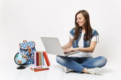 Portrait of young smiling woman student holding using laptop pc computer sitting near globe, backpack, school books. Isolated on white background. Education in stock photography