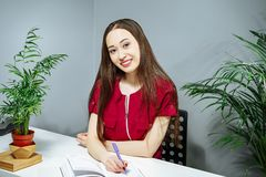 Portrait of a young smiling woman taking notes in a notebook stock photography