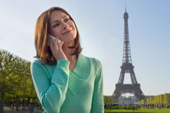 Portrait of a young smiling woman talking on the phone in Paris. France with Eiffel Tower in background. Cute beautiful Caucasian female model holding a phone in Stock Photos