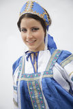 Portrait of young smiling woman in traditional clothing from Russia, studio shot Stock Image