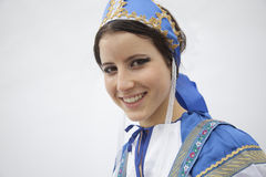 Portrait of young smiling woman in traditional clothing from Russia, studio shot Stock Photos