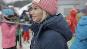 Portrait of a young smiling woman waiting for her friends near ski lift. stock footage