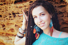 Portrait of a young smiling woman wearing dreadlocks hairstyle, dressed in blue lace dress and blue boho chic earrings Stock Photography