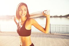 Portrait young smiling woman with white towel. Portrait young attractive smiling fit woman with white towel resting after workout sport exercises outdoors on a Royalty Free Stock Photos