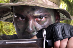Portrait of a young soldier painted with jungle camouflage royalty free stock photo