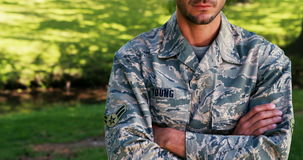 Portrait of soldier standing with arms crossed in park stock video footage