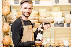Cheese seller portrait. Portrait of a young sommelier in uniform standing with wine bottle in front of the store showcase full of different cheeses royalty free stock images