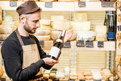 Cheese seller portrait. Portrait of a young sommelier in uniform standing with wine bottle in front of the store showcase full of different cheeses stock images