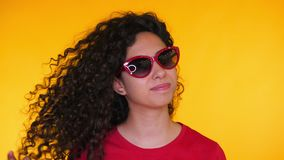 Portrait of young spanish girl with curls puts on sunglasses on yellow background. Tempting woman smiling to camera stock footage