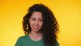 Portrait of young spanish student girl with curls on yellow background. Trendy cute woman smiling to camera. Studio. Footage. Female in green t-shirt, casual stock video
