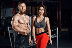 Portrait of a young sport couple in the gym. Fitness concept background Stock Images